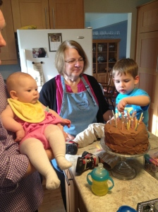 Jamie helping add candles to Grandpa's cake with Lizzie supervising.